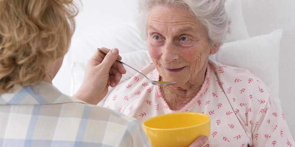 Женщина кормит бабушку
